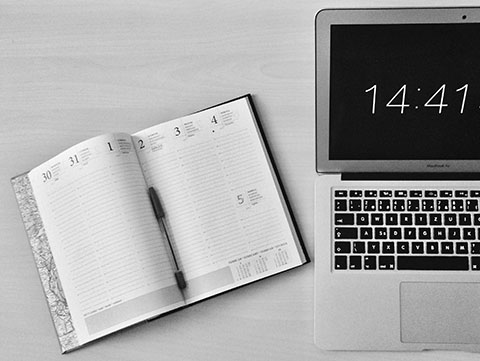 Open Macbook and planner for scheduling.